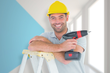 power drill: Male technician holding power drill on ladder against modern blue and white room Stock Photo
