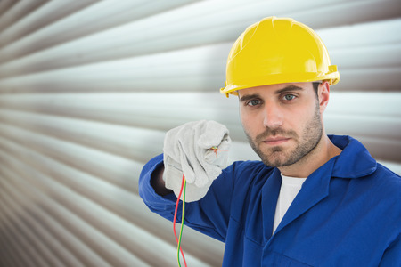 repairman: Confident repairman holding cables against grey shutters Stock Photo