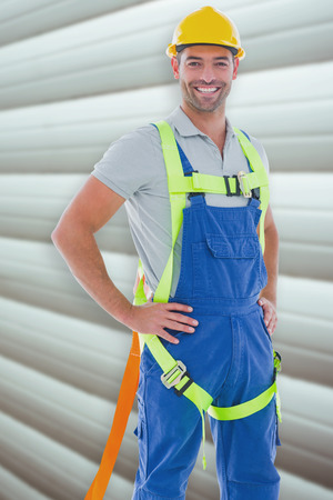 safety gear: Builder in safety gear against grey shutters Stock Photo