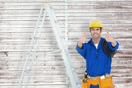 Happy electrician gesturing thumbs up by ladder against digitally generated grey wooden planks photo