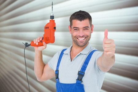 Smiling repairman with drill machine gesturing thumbs up against grey shutters
