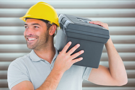 shoulder carrying: Handyman carrying toolbox on shoulder against grey shutters Stock Photo