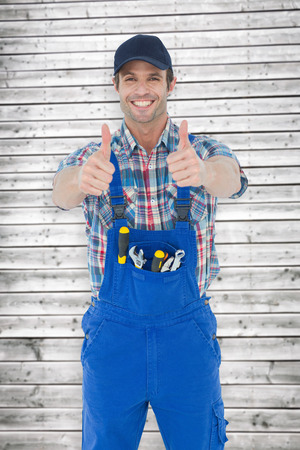 Confident plumber showing thumbs up sign against digitally generated grey wooden planks photo
