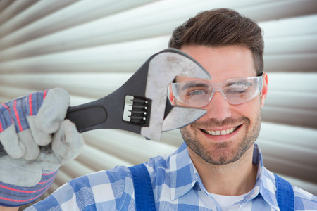 protective glasses: Confident repairman wearing protective glasses while holding wrench against grey shutters