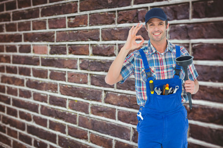 Plumber holding plunger while gesturing OK sign against red brick wall photo