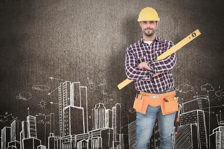 spirit level: Smiling handyman holding spirit level  against hand drawn city plan Stock Photo