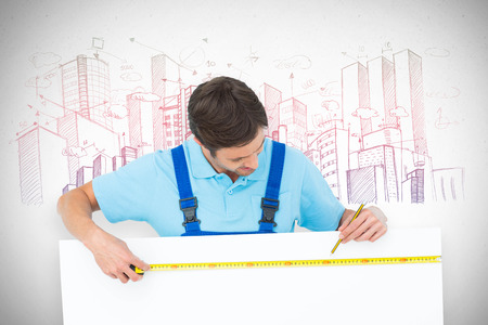 bill board: Carpenter measuring blank bill board against grey Stock Photo