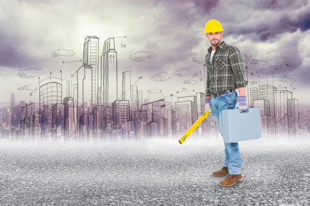 Manual worker with spirit level and toolbox against black road photo