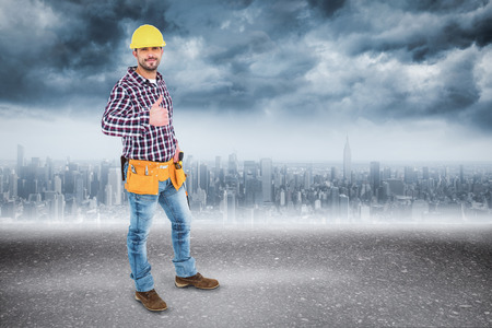 Smiling handyman gesturing thumbs up against road photo