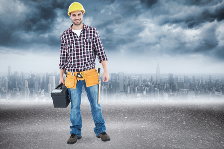 Happy male hanyman carrying toolbox against road photo