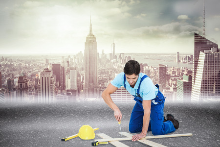 Repairman fixing screw on plank against road photo