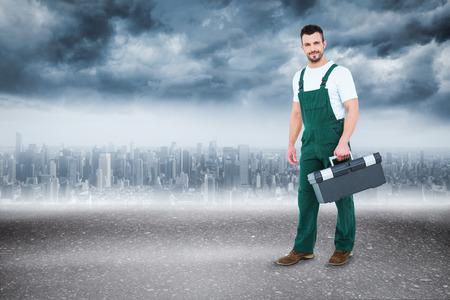 Repairman holding toolbox  against road photo