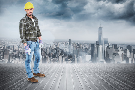 Full length portrait of confident handyman against room with large window looking on city photo
