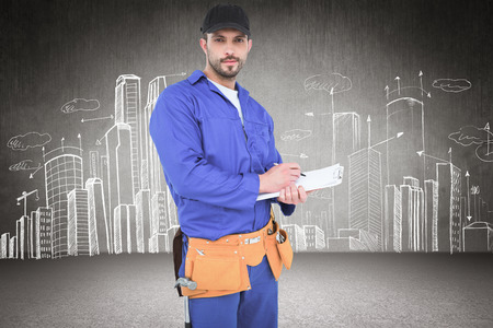 blue overall: Handyman in blue overall writing on clipboard against hand drawn city plan