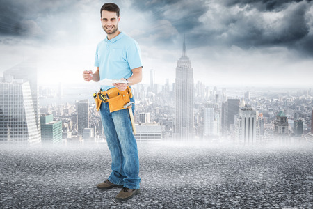 Smiling construction worker holding clipbard against black road photo