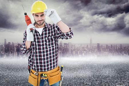 Confident handyman holding drill machine against black road photo