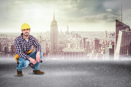 power drill: Crouching handyman holding power drill against road