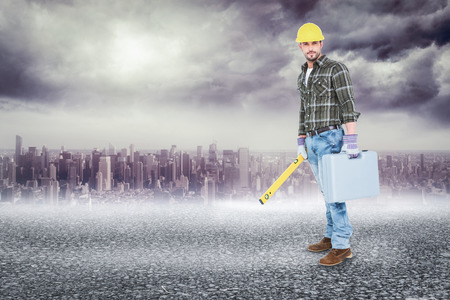 spirit level: Manual worker with spirit level and toolbox against black road