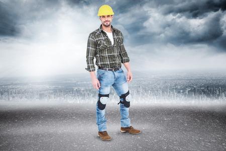 Full length portrait of confident handyman against road photo