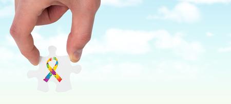 Hand holding jigsaw piece against blue sky photo