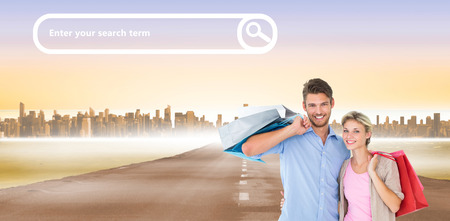man and woman with shopping bags: Attractive young couple holding shopping bags against city on the horizon