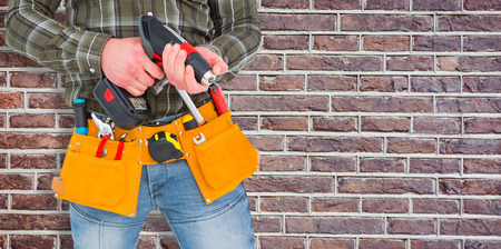 power drill: Manual worker holding gloves and hammer power drill  against red brick wall