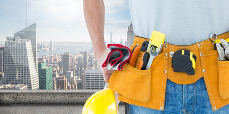 Technician with tool belt around waist against large city Stock Photo