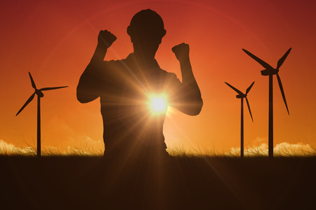 Excited manual worker clenching fists against sky and field photo