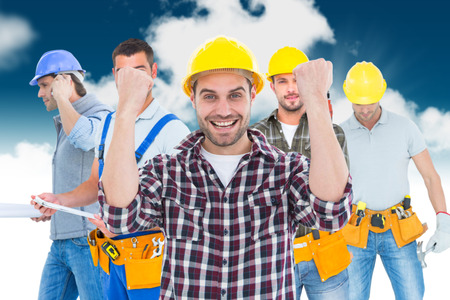 clenching fists: Composite image of successful male handyman clenching fists