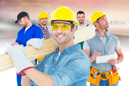 hardhat: Composite image of carpenter wearing hardhat and glasses while carrying wooden planks Stock Photo