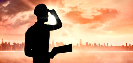 hardhat: Manual worker wearing hardhat while holding clipboard against sun shining over city Stock Photo