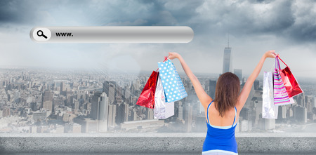 christmas shopping bag: Rear view of a brunette woman raising shopping bags against large city
