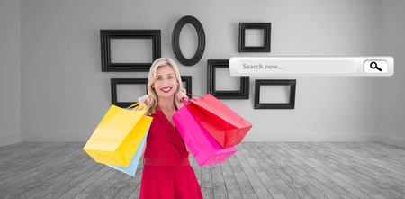 Stylish blonde in red dress holding shopping bags against big room with several frames at wall photo