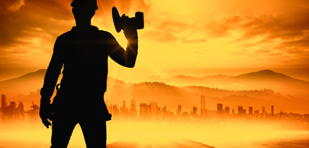power drill: Handyman wearing tool belt while holding power drill against sun shining over road and city
