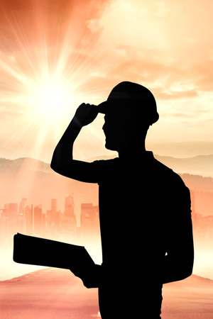 hardhat: Manual worker wearing hardhat while holding clipboard against sun shining over road and city Stock Photo