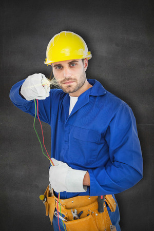 repairman: Confident repairman holding cables against black wall