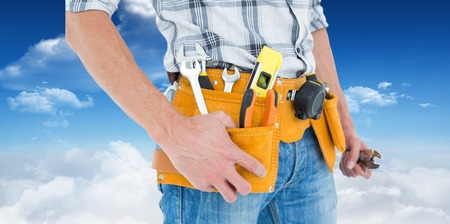 Cropped image of technician with tool belt around waist against bright blue sky with clouds photo