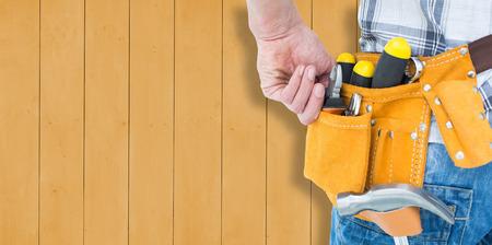 Technicien avec l'outil ceinture autour de la taille contre les planches de bois Banque d'images