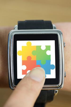 Businesswoman with smart watch on wrist against autism awareness jigsaw Stock Photo