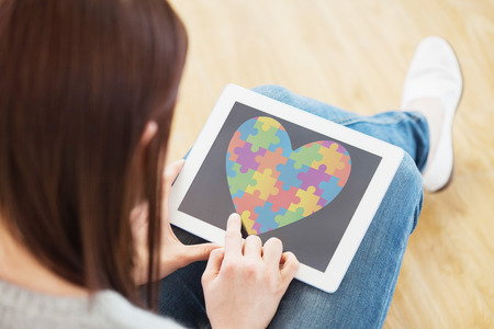 autism: Girl using a tablet pc sitting on the floor against autism awareness heart Stock Photo