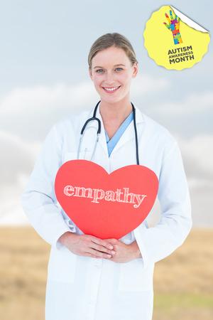 empatia: La palabra empat�a y m�dico que sostiene la tarjeta de coraz�n rojo contra el paisaje marr�n brillante