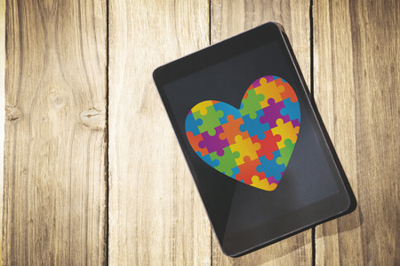 autism: Autism awareness heart against overhead of tablet on desk