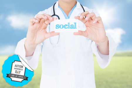 The word social and doctor holding card  against sunny green landscape photo