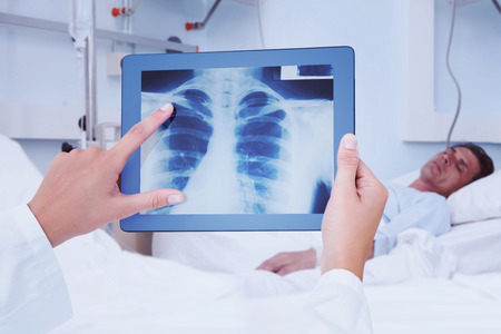 sleeping tablets: Composite image of doctor looking at xray on tablet