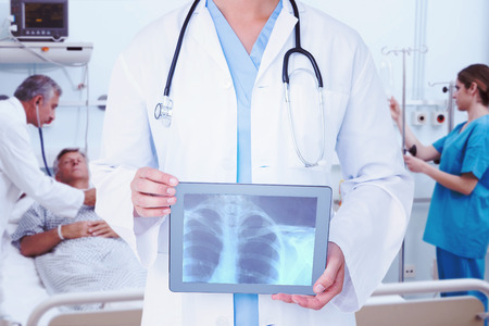 Composite image of doctor looking at xray on tablet photo