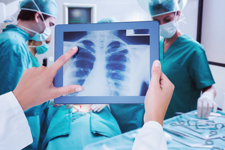 surgical tray: Composite image of doctor looking at xray on tablet
