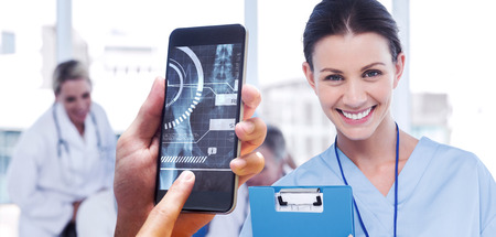 hand holding smartphone against cheerful young surgeon posing with colleagues in background photo