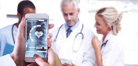 Hand holding smartphone against doctors using a tablet Stock Photo