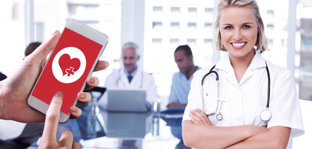 Hand holding smartphone against nurse with arms crossed photo