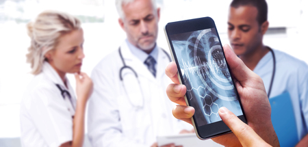 hand holding smartphone against three doctors using a tablet
